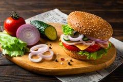 Hamburger de sandwich avec du jambon, le fromage et des légumes sur un conseil en bois avec des ingrédients Copiez l'espace Alime images stock