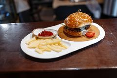 Hamburger decorated tomato, french fries and tomato sauce in a oval plate on a wooden table stock image