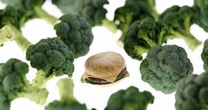 Hamburger degli alimenti a rapida preparazione contro le verdure sane immagine stock