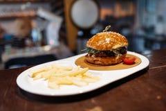 Hamburger dekorujący pomidor, francuzów dłoniaki i pomidorowy kumberland w owalu talerzu na drewnianym stole, zdjęcia royalty free