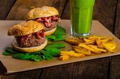 Hamburger del bacon con il frullato della banana delle fritture e delle erbe dei peperoncini rossi fotografie stock