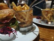 Hamburger del bacon del formaggio con le patatine fritte ed il cavolo rosso selezionato fotografia stock libera da diritti