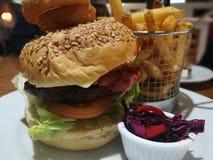 Hamburger del bacon del formaggio con le patatine fritte ed il cavolo rosso selezionato immagine stock libera da diritti