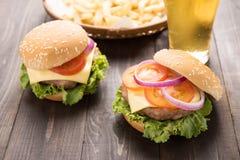 Hamburger del Bbq con le patate fritte e la birra sul backgroun di legno Fotografie Stock Libere da Diritti