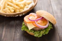 Hamburger del Bbq con le patate fritte sui precedenti di legno Fotografie Stock