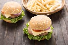 Hamburger del Bbq con le patate fritte sui precedenti di legno Immagini Stock