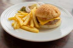 Hamburger del formaggio con le patate fritte sulla tavola Immagine Stock Libera da Diritti