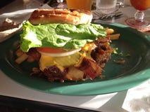 Hamburger del formaggio del bacon fritto nel grasso bollente Immagini Stock Libere da Diritti