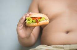 Hamburger del formaggio del pollo sulla mano grassa obesa del ragazzo Fotografia Stock