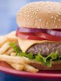 Hamburger del formaggio in un panino del seme di sesamo con le fritture Fotografia Stock Libera da Diritti