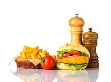 Hamburger del pollo con le patate fritte ed i condimenti Immagini Stock Libere da Diritti