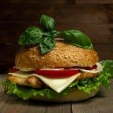 Hamburger delicioso com queijo, tomates e manjericão no fundo de madeira Refeição do Fastfood fotografia de stock royalty free