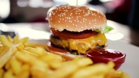 Hamburger delicioso com uma costeleta grande e um frasco das batatas fritas com ketchup video estoque