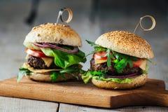 Hamburger deliziosi con manzo, il pomodoro, il formaggio e la lattuga Immagine Stock