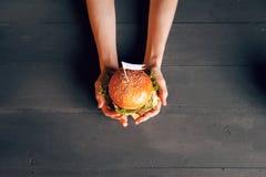 Hamburger delizioso a disposizione Fotografia Stock