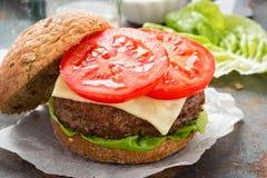 Hamburger della bistecca con lattuga verde, fette di pomodori e cipolle arrostite - i peperoncini rossi dolci immergono immagini stock libere da diritti