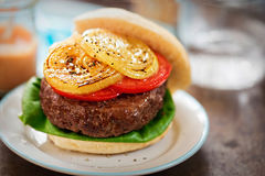 Hamburger della bistecca con lattuga verde, fette di pomodori e cipolle arrostite - i peperoncini rossi dolci immergono fotografie stock