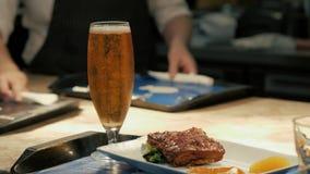 Hamburger della carne e della birra sulla tavola di legno in vassoio del ristorante del caffè video d archivio