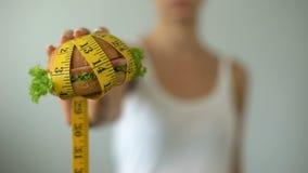 Hamburger della tenuta della ragazza avvolto in nastro di misurazione, alimenti industriali, stile di vita non sano stock footage