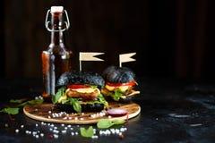 Hamburger deux noir avec la côtelette, les verts, le fromage, les oignons et les tomates et une bouteille de bière d'un plat en b photo stock