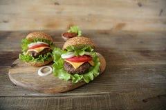 Hamburger deux parfait avec le petit pâté de boeuf, fromage, conserves au vinaigre, tomates, oignon, laitue sur un fond rustique  photographie stock