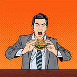 Hamburger di Art Business Man Eating Tasty di schiocco sul lavoro Immagini Stock
