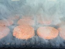 Hamburger, die auf dem Sommergrill rauchen Stockbild