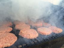 Hamburger, die auf dem Sommergrill rauchen Stockfotografie