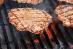 Hamburger do BBQ na grade com flamas Fotos de Stock Royalty Free