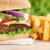 Hamburger do cheeseburger com fim do close up das fritadas acima Imagem de Stock