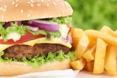 Hamburger do cheeseburger com fim do close up das fritadas acima do chee dos tomates Imagem de Stock