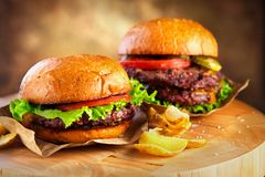 Hamburger and Double Cheeseburger with fries wooden table background. Cheeseburgers on fresh buns with succulent beef. And fresh salad ingredients served with royalty free stock photo