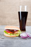 Hamburger and drink on wooden table Royalty Free Stock Photos