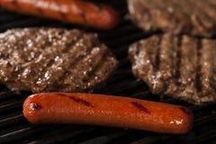 Hamburger e cachorros quentes na grade Fotografia de Stock Royalty Free
