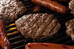 Hamburger e cachorros quentes na grade Fotos de Stock Royalty Free
