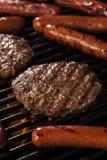 Hamburger e cachorros quentes na grade Foto de Stock