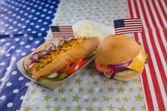 Hamburger e hot dog sulla tavola di legno con il tema del 4 luglio Fotografia Stock