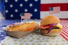 Hamburger e hot dog sulla tavola di legno con il tema del 4 luglio Fotografie Stock Libere da Diritti