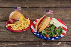 Hamburger e hot dog sulla tavola di legno con il tema del 4 luglio Immagine Stock