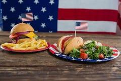 Hamburger e hot dog sulla tavola di legno con il tema del 4 luglio Fotografia Stock Libera da Diritti