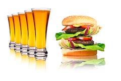 Hamburger e linha dobro de cervejas Fotografia de Stock Royalty Free
