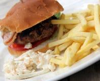 Hamburger e microplaquetas e salada de repolho Imagens de Stock