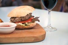 Hamburger e vinho Imagens de Stock