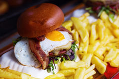 Hamburger with egg, bacon and french fries Royalty Free Stock Images