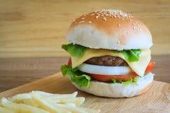 Hamburger en Franse frieds op houten scherpe raad Stock Foto