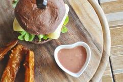 Hamburger en frieten op de houten plaat royalty-vrije stock afbeelding