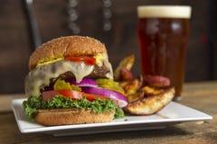 Hamburger en gebraden gerechten samen met bier wordt gediend dat Royalty-vrije Stock Fotografie