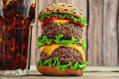Hamburger et kola avec de la glace sur un fond en bois Image libre de droits
