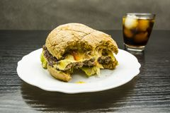 Hamburger et kola mordus de boeuf avec de la glace dans un verre dans le backgroun Images stock
