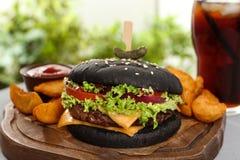 Hamburger et pommes frites noirs juteux sur le conseil en bois photographie stock libre de droits